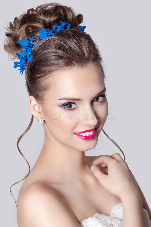 Fashion portrait of a beautiful attractive girl with a gentle elegant evening wedding hairstyles high and bright make-up with flow. Fashion portrait of a stock images