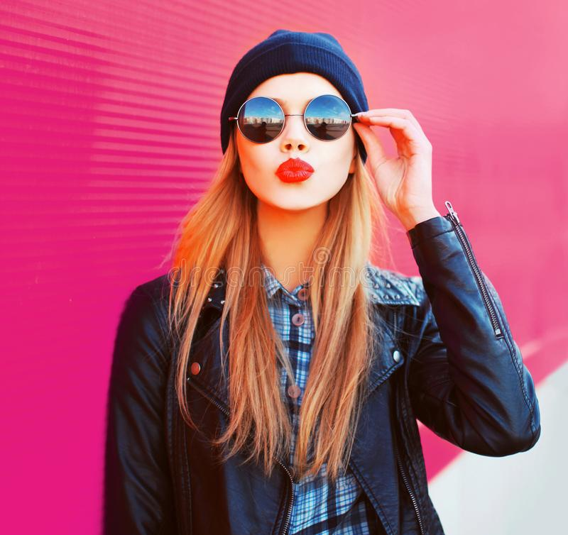 Fashion portrait beautiful blonde woman sending sweet air kiss in rock black style jacket, hat on city street over colorful pink royalty free stock photos