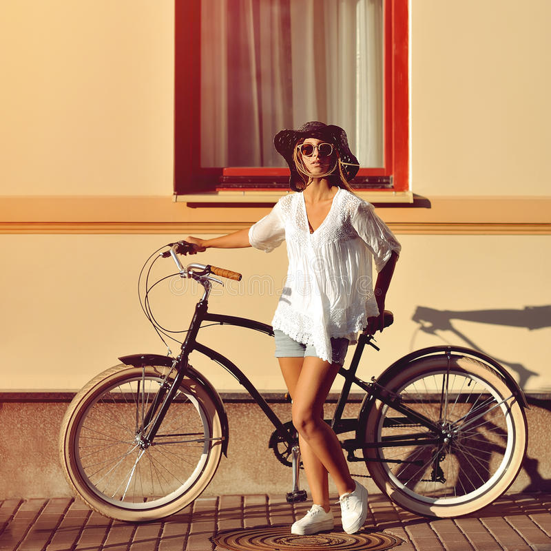 Fashion portrait of beautiful female model on a vintage bike royalty free stock photography