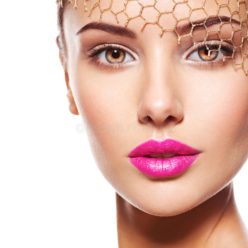 Fashion portrait of a beautiful girl wears golden veil on face. Pink lips. Isolated on white background royalty free stock photography