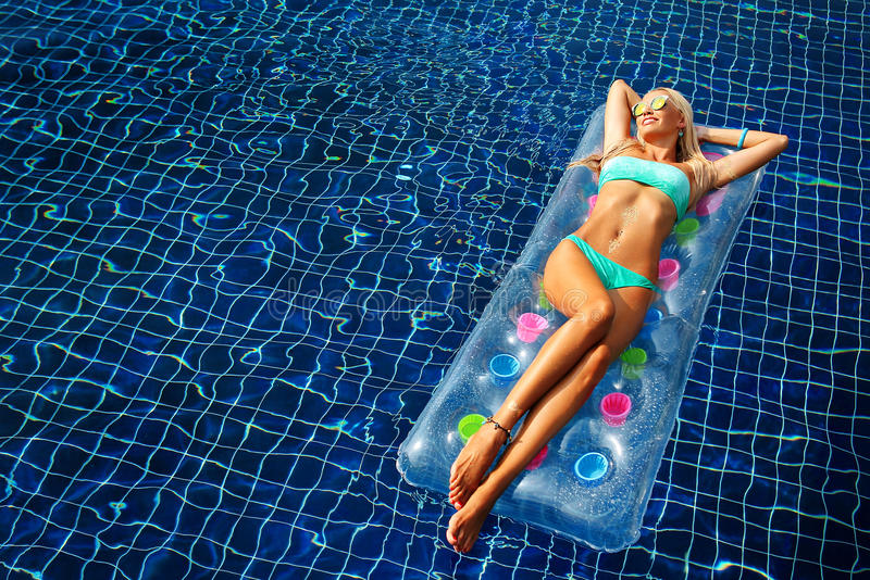 Fashion portrait of beautiful tanned woman with blond hair in elegant bikini relaxing on a swimming pool royalty free stock image