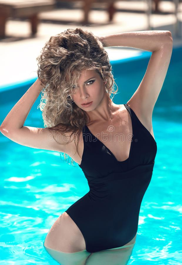 Fashion portrait of beautiful tanned woman with blond hair in elegant black bikini relax in blue swimming pool royalty free stock photo