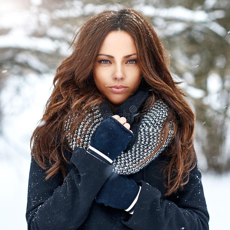 Fashion portrait of a beautiful winter woman in snowy weather in. Winter park royalty free stock images