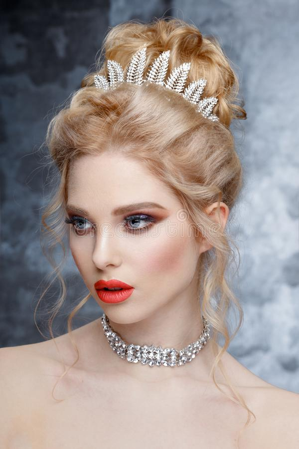Fashion Portrait of Beautiful Woman with Tiara on head. Elegant Hairstyle. Perfect Make-Up and Jewelry. Coral Lips stock images