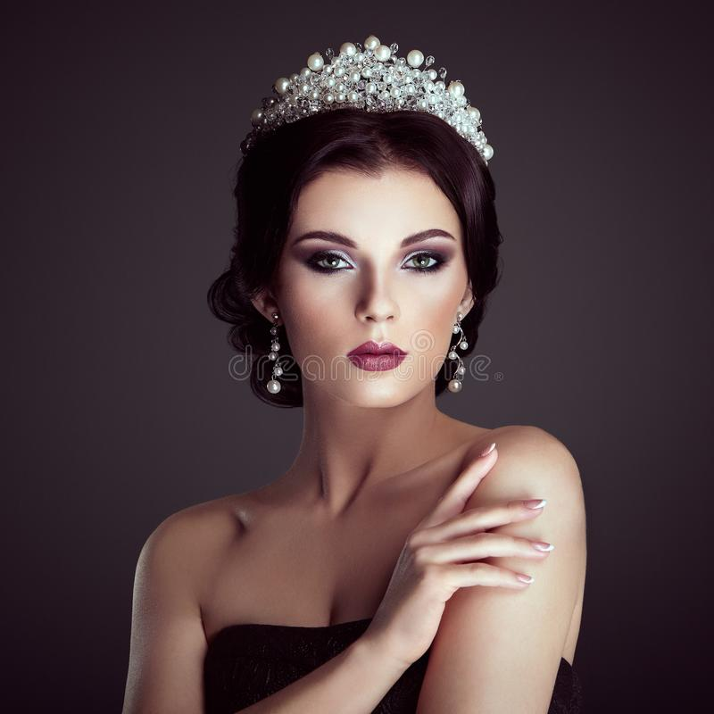 Fashion portrait of beautiful woman with tiara on head. Elegant Hairstyle. Perfect Make-Up and Jewelry. Red Lips royalty free stock photography
