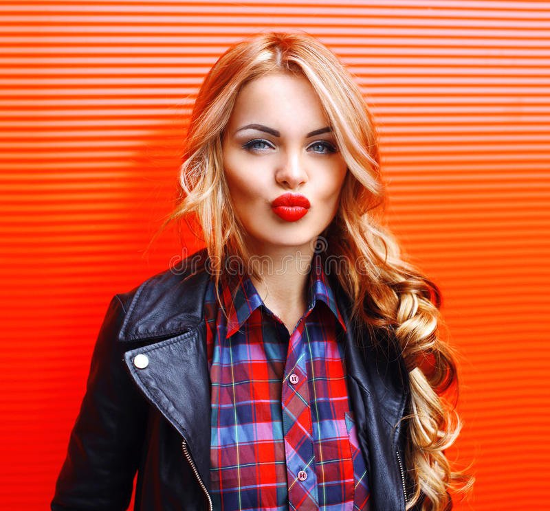 Fashion portrait beautiful young blonde woman blowing red lips making kiss wearing a black rock style over colorful stock photos