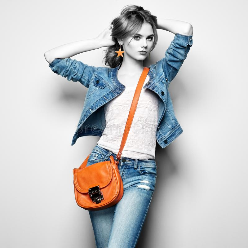 Fashion portrait of beautiful young woman with handbag. Fashion Portrait of Beautiful Young Woman with dark Hair. Girl in Blouse and Jeans. Jewelry and Hairstyle stock photo