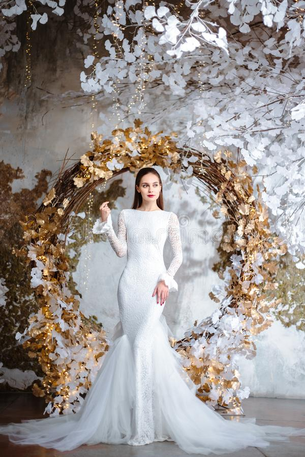 Fashion portrait of beautiful young woman in a gorgeous wedding dress. Posing in a fantasy interior with white winter tree stock photos