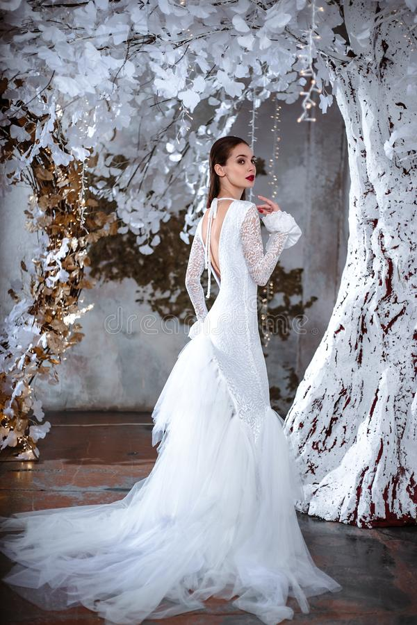 Fashion portrait of beautiful young woman in a gorgeous wedding dress. Posing in a fantasy interior with white winter tree royalty free stock images