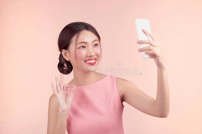 Fashion portrait of a beautiful young woman in a pretty dress over pink background.  stock photos