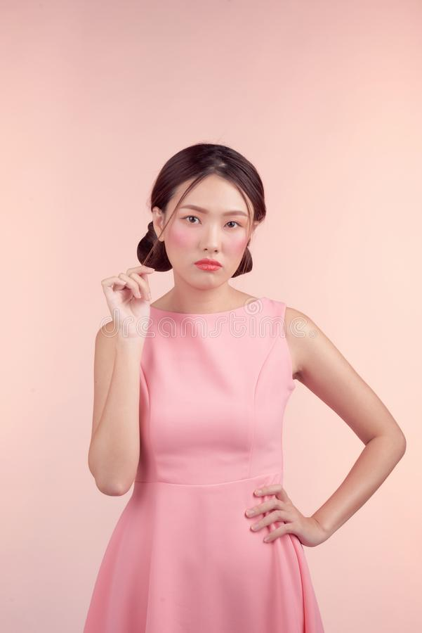 Fashion portrait of a beautiful young woman in a pretty dress over pink background.  stock photo