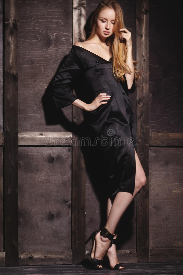 Fashion portrait of beautiful young woman in black dress near with wood wall. Elegant dark evening look royalty free stock images