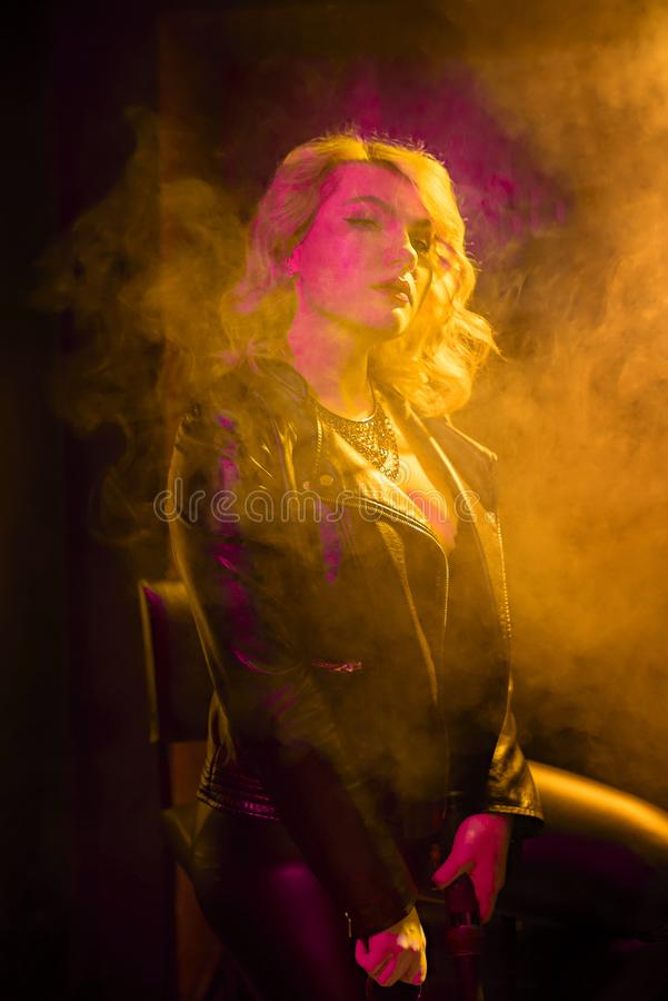 Fashion portrait of beauty trendy young model woman in club, bright lights with lots of colorful smoke,  neon light. Night life royalty free stock images