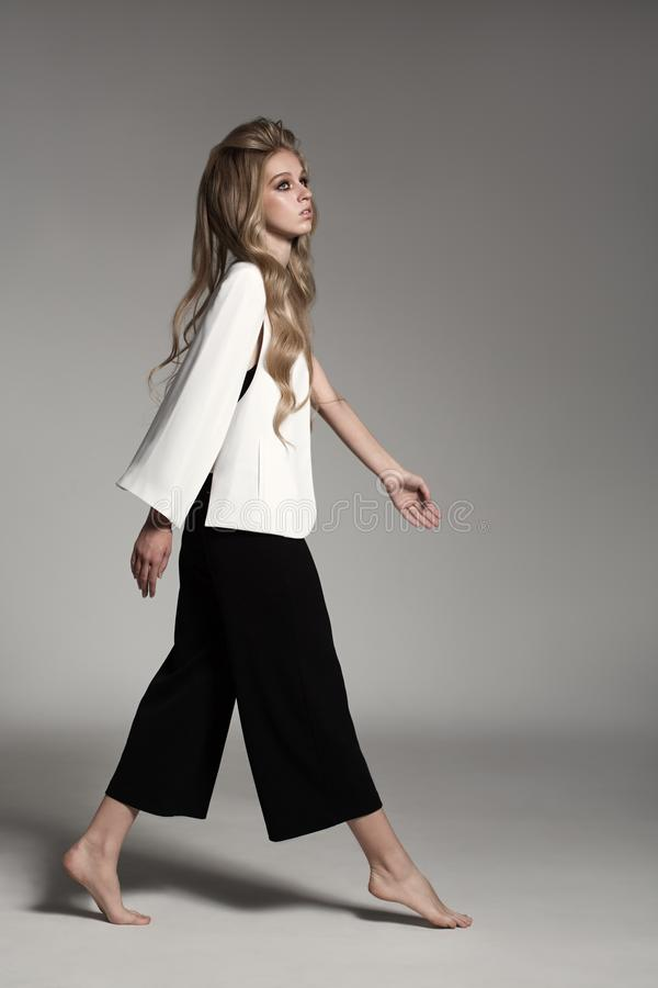 Fashion portrait of blonde woman dressed white jacket and black breeches. Fashion portrait of woman dressed white jacket and black breeches stock image