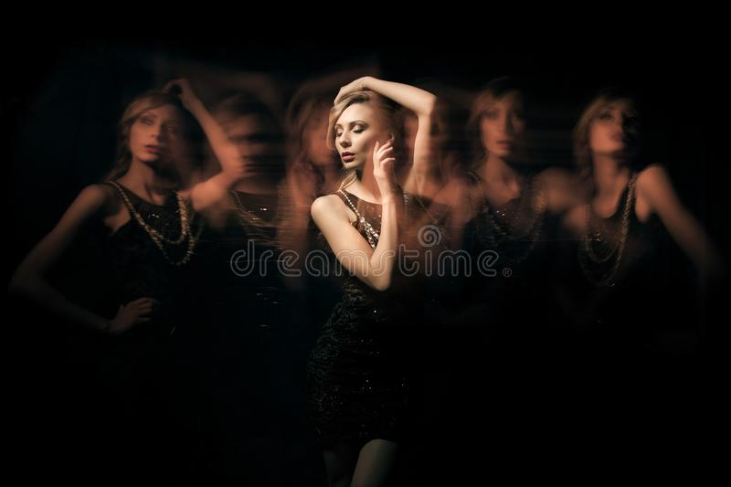 Fashion portrait of blondie lady in dark dress with six translucent clone. Shooting in mixed light technique stock image