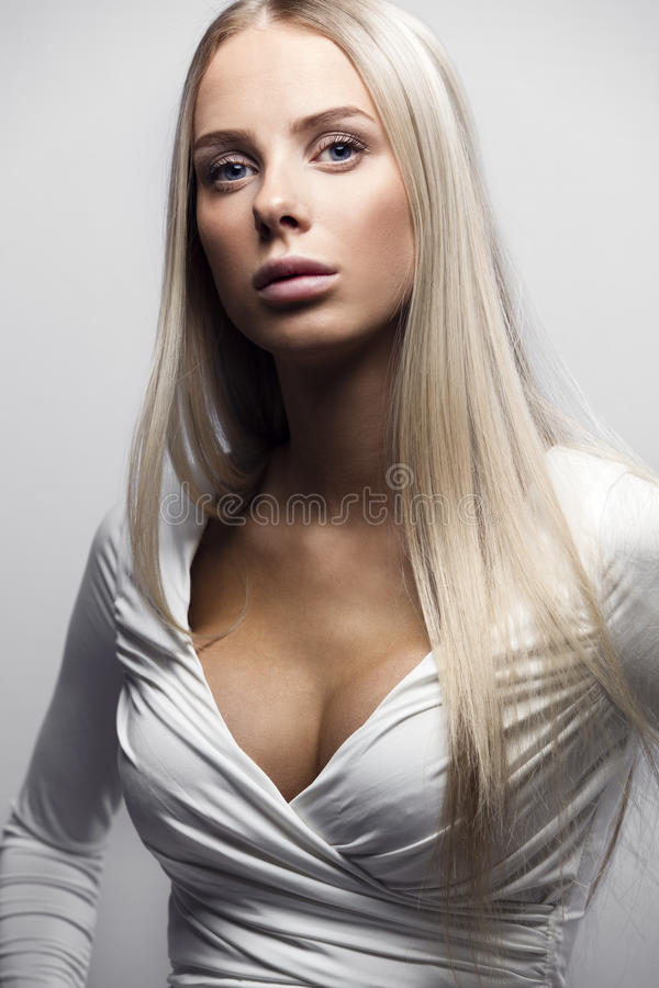 Fashion portrait of a confident blonde woman in white dress stock photo