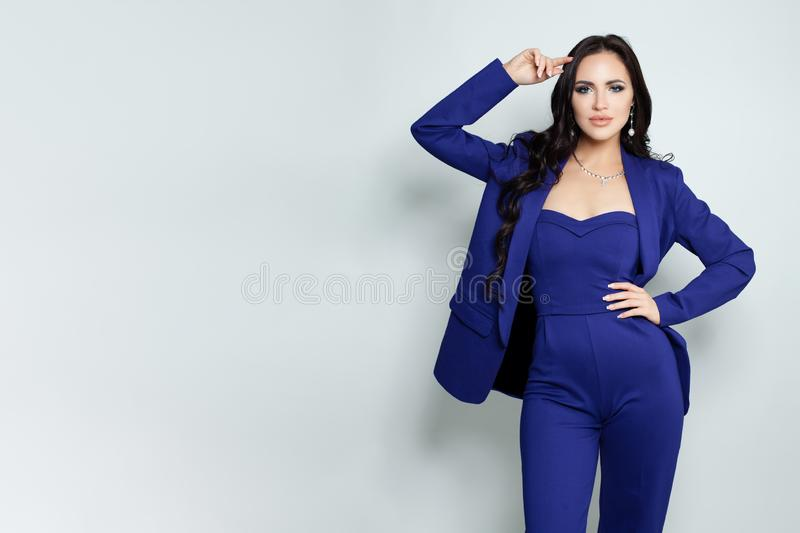 Fashion portrait of elegant model woman in jumpsuit standing against white background stock photography
