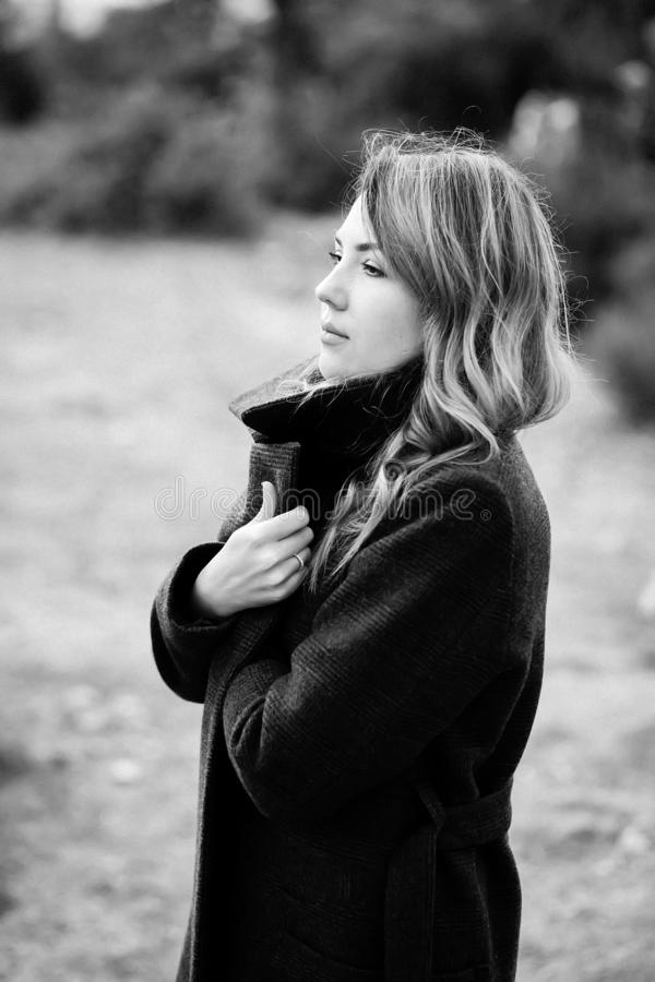 Fashion portrait of elegant woman in black and white color wearing black stylish coat. Sensual scene of yang sad lady dreaming of stock image