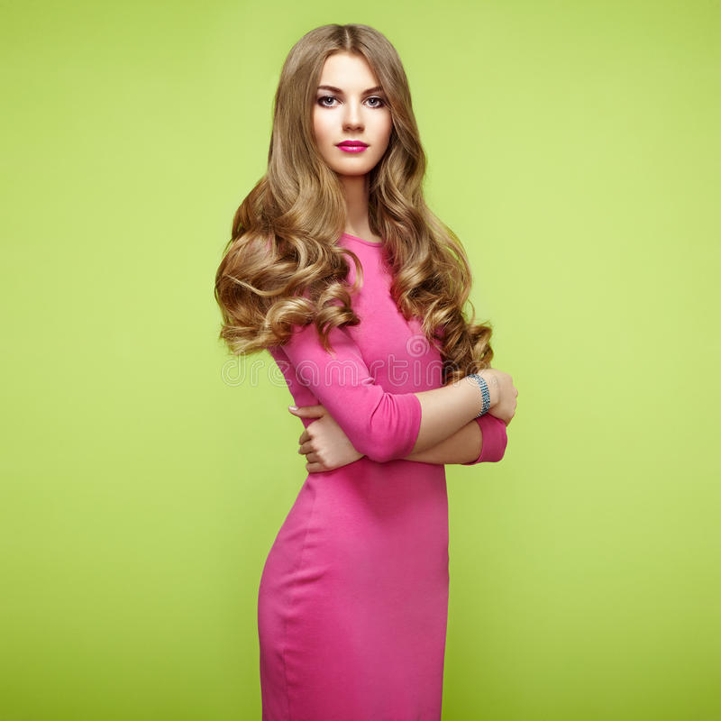Fashion portrait of elegant woman with magnificent hair. Blonde girl. Perfect make-up. Girl in pink dress on green background royalty free stock photography