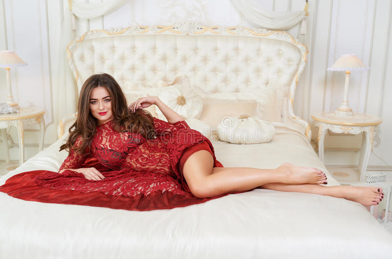 Fashion portrait of elegant young woman in red dress in luxurious interior royalty free stock photos