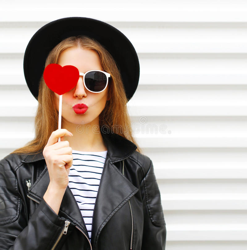 Free Fashion Portrait Face Pretty Sweet Young Woman With Red Lips Making Air Kiss With Lollipop Heart Wearing Black Hat Leather Jacket Royalty Free Stock Photo - 79064315