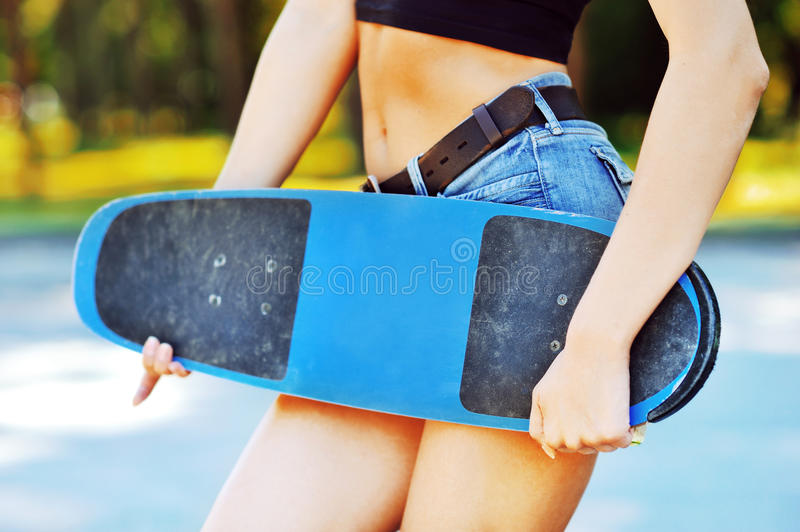 Fashion portrait of female hands holding a skateboard - closeup. Outdoors royalty free stock image