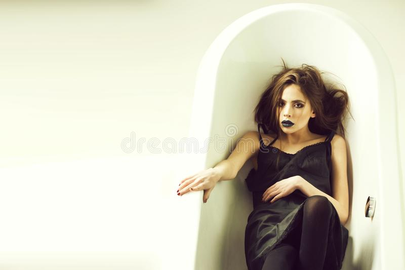 Fashion portrait of a girl in a bath. woman in dress with long hair, black lipstick in bath royalty free stock photography