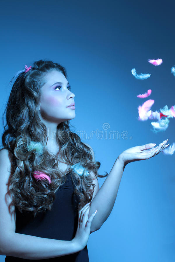 Fashion portrait of girl with feathers. In blue light royalty free stock photography