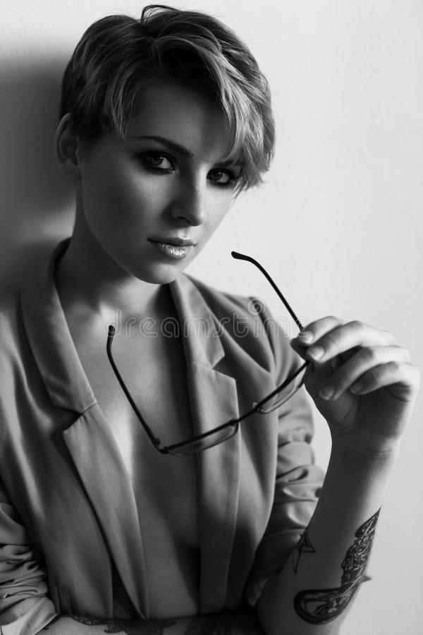 Fashion portrait of a girl with short hair wearing a jacket with glasses in ha. Nd. Black and white photo stock images