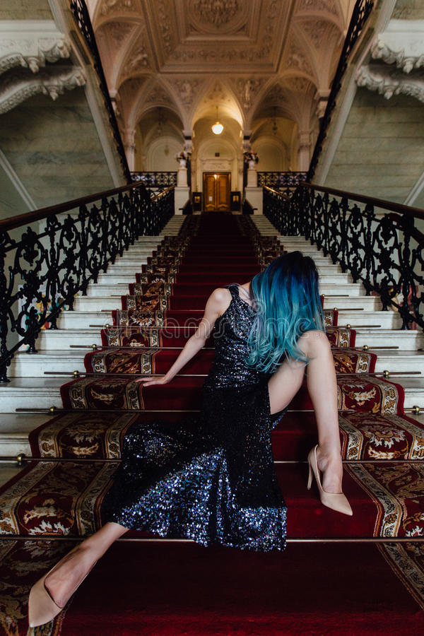 Fashion portrait of gorgeous girl with blue dyed hair long. The beautiful evening cocktail dress. royalty free stock image