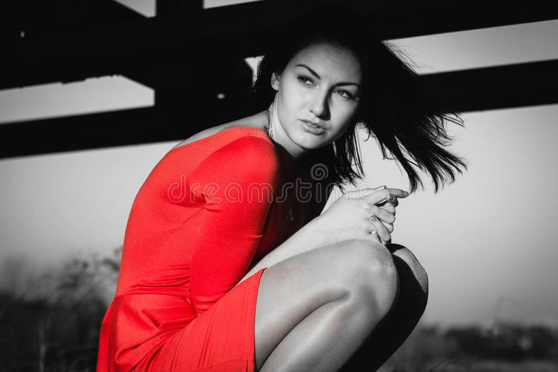 Fashion portrait of gorgeous sensual woman with dark hair wears elegant red dress. She is stting. Emphasis on red royalty free stock photo