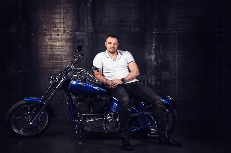 Fashion portrait of a handsome young athletic man sitting on a shiny cool motorbike in his garage royalty free stock image