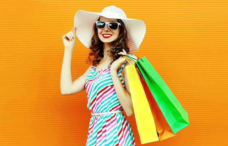 Fashion portrait happy smiling woman with shopping bags wearing colorful striped dress, summer straw hat posing on orange wall stock images