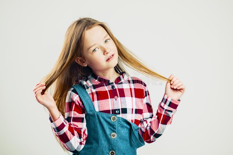 Fashion portrait of a little girl. handsome kid posing in the studio. Children raised up hair royalty free stock images