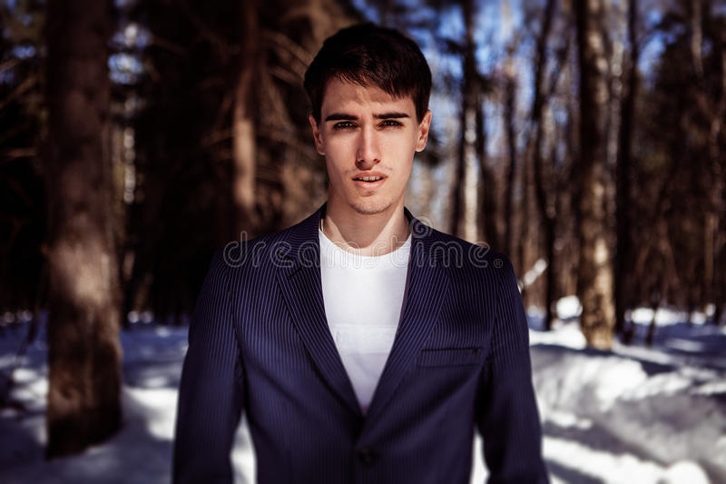 Fashion portrait of a man in snow forest in vogue style stock images