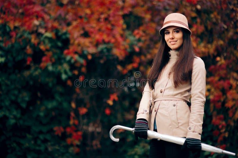 Autumn Woman Wearing a Rain Coat Holding an Umbrella royalty free stock photo