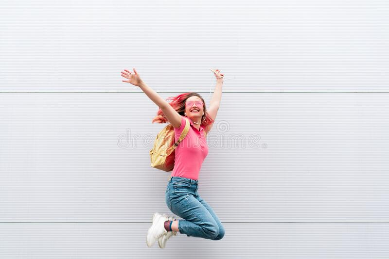 Fashion portrait of pretty smiling hipster woman in sunglasses and colored red hairs with smartphone against the. Colorful grey wall. Jumping. Copyspace stock photos