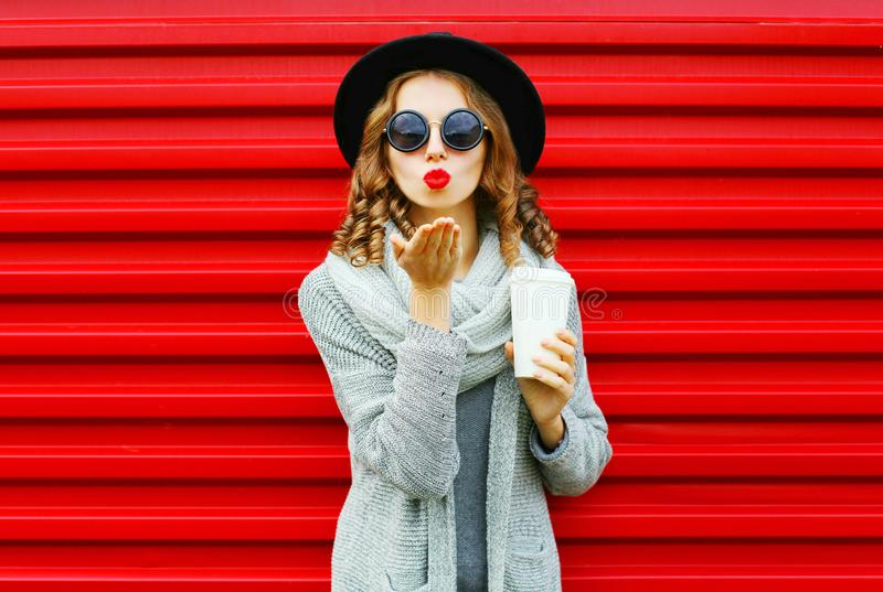 Fashion portrait pretty woman with coffee cup blows red lips royalty free stock images