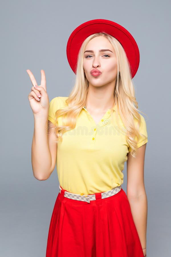 Fashion portrait pretty woman with victory sign in color style over gray background stock images