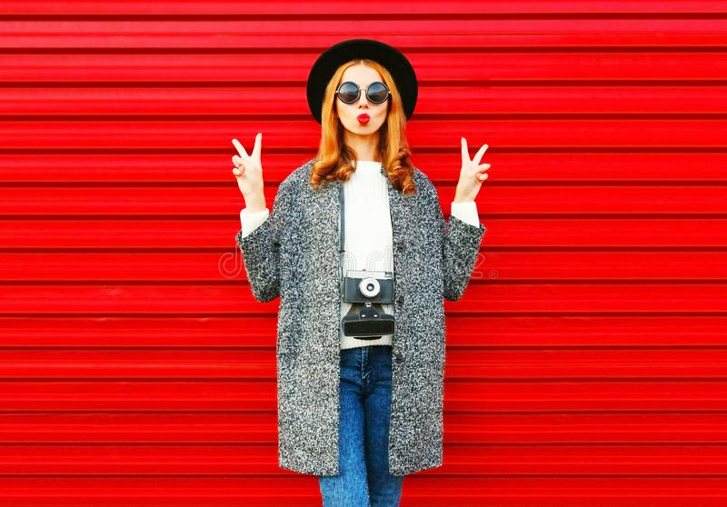 Fashion portrait pretty woman with retro camera posing on a red stock image