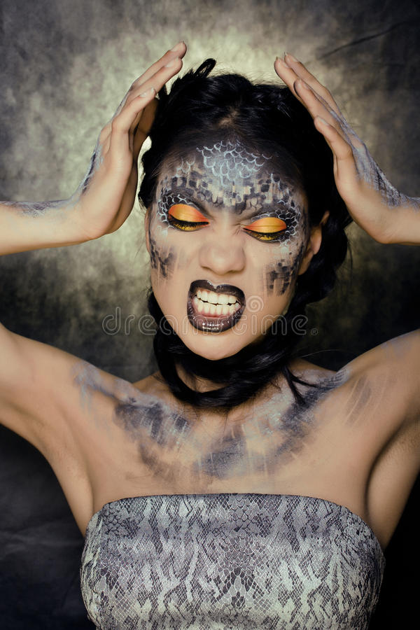 Fashion portrait of pretty young woman with creative make up like a snake royalty free stock images