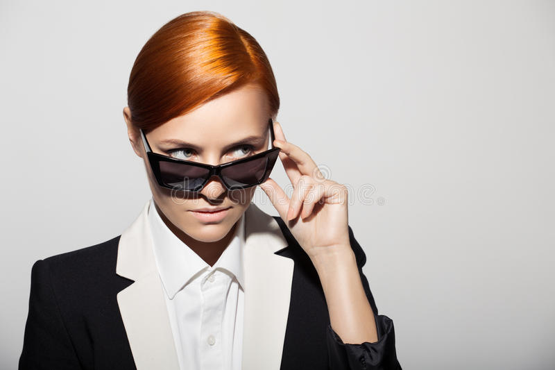 Fashion portrait of serious woman dressed as a secret agent stock photography