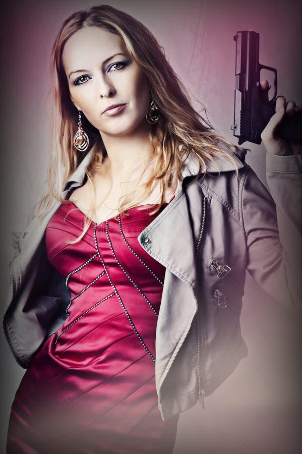 Fashion portrait of woman with gun. Fashion portrait of dangerous woman holding gun royalty free stock images