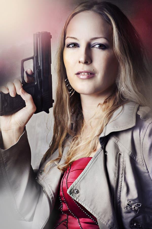 Fashion portrait of woman with gun. Fashion portrait of dangerous woman holding gun royalty free stock photo