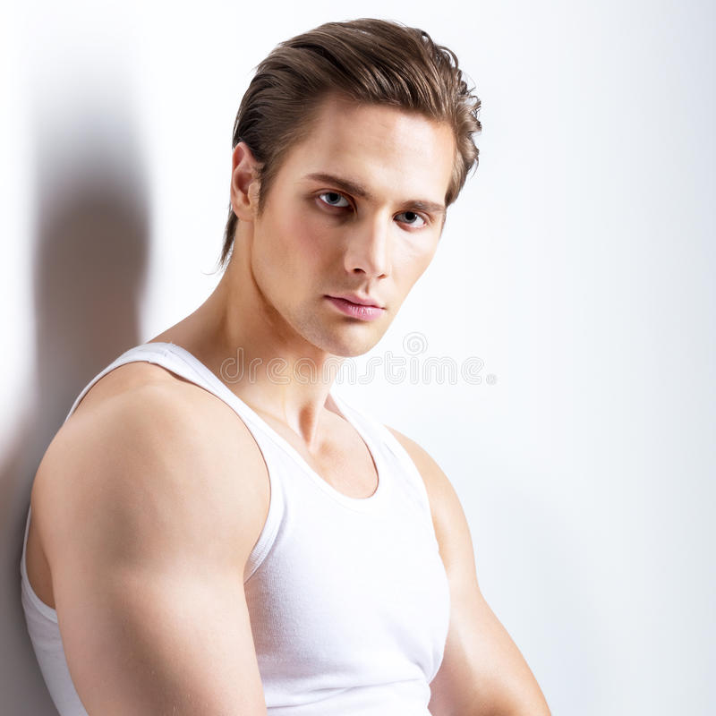 Fashion portrait of young man. Fashion portrait of young man in white shirt poses over wall with contrast shadows royalty free stock photography
