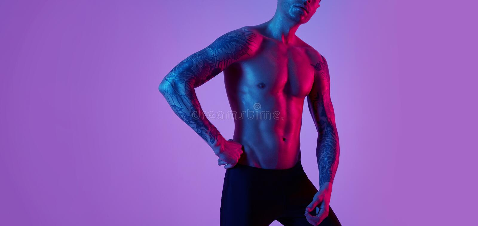 Fashion portrait of sport fit attractive man. Masculine naked torso tattooed hands. Color flash studio light stock image