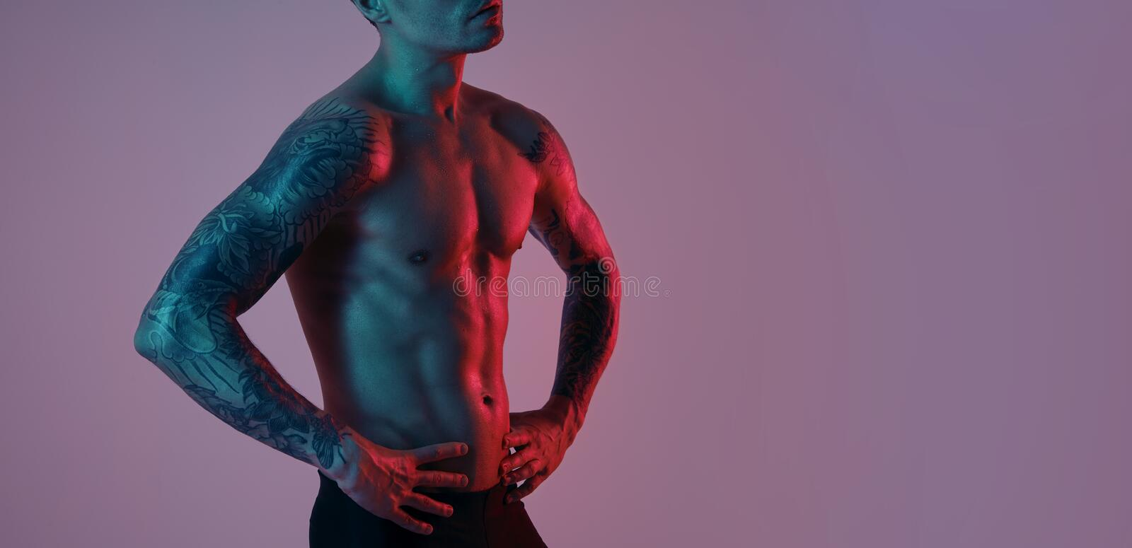 Fashion portrait of sport fit attractive man. Masculine naked torso tattooed hands. Color flash studio light.  royalty free stock photography