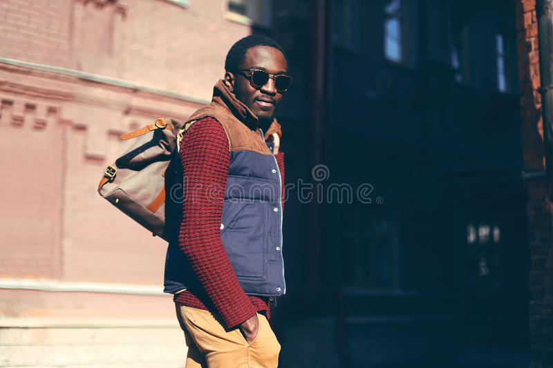 Fashion portrait stylish african man wearing bag in evening stock image
