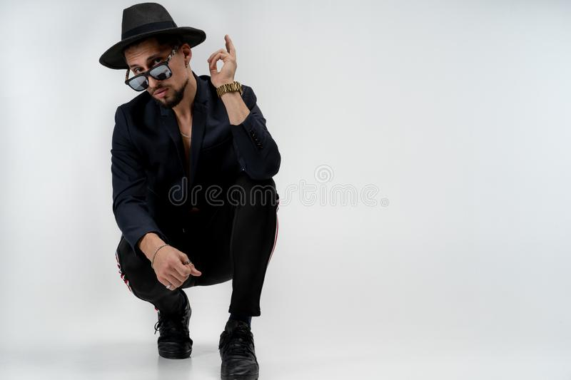 Fashion portrait of stylish bearded young man in trendy suit and hat in black sunglasses, showing ok sign, isolated over stock photo