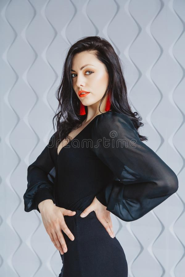 Fashion portrait of a stylish brunette girl wearing a black dress. Woman with long hair wearing red earrings. Posing in stock photos
